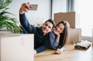 A young couple with a smartphone moving in a new home, taking selfie.