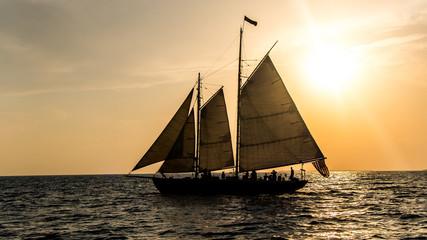 Sailboats at sunset under sail and at the docks