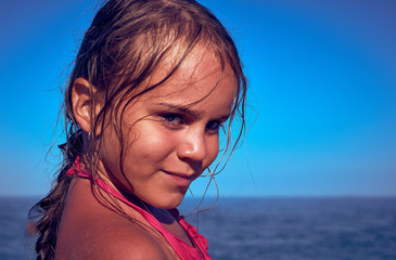 Portrait of a tanned little girl on the background of the sea.