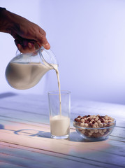 Pours Milk on wooden background close-up shot