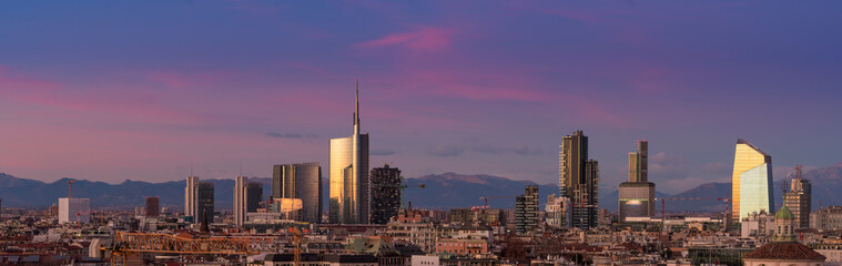Spoed Fotobehang Milan Aerial view of Milan skyline at sunset with alps mountains in the background.