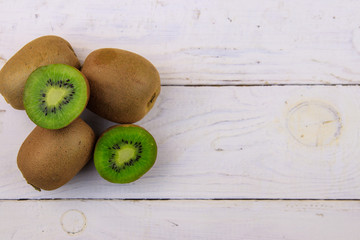 Kiwi fruits on white wooden table. Top view, copy space