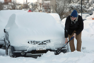 A man shovels around a car after a winter storm in Buffalo, New York