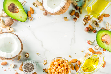 Healthy vegan fat food sources, omega3, omega6 ingredients - almond, pecan, hazelnuts, walnuts, olive oil, chia seeds, avocado, coconut,  banner copy space