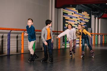 Laughing kids in roller skates enjoying leisure
