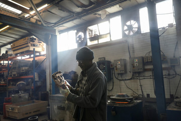 A foundry worker poses for a photograph with a British Academy of Film and Television Awards (BAFTA) mask at a foundry in west London