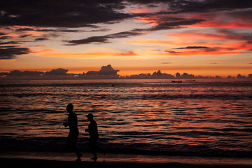 Background sky sunset,Silhouette Jogging on the beach,Bright in Phuket Thailand.