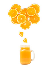 glass with fresh orange juice is standing under many orange slices on white background