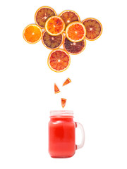 glass with fresh blood orange juice is standing under many blood orange slices on white background