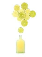 bottle with fresh lime juice is standing under many lime slices on white background