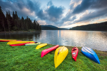 Colorful canoes on the beach / Beautiful summer morning view of Beglik dam in Rhodopi Mountains, Bulgaria with colorful canoes scattered on the grass to dry
