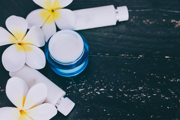 mixed skincare and beauty products with flowers and seashells on dark wood background