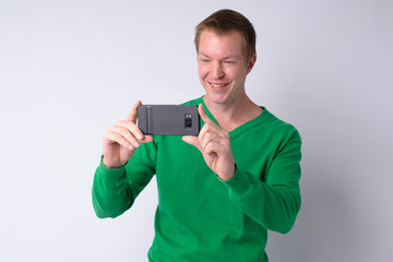 Happy young handsome man taking picture with phone