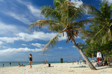 Koh Phangan, Thailand - December 20, 2018: Tourists are enjoying traditional idyllic holiday in asia - Zen beach in Thailand with coconut palm tree, blue sky and white sand.