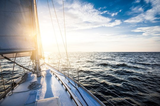 White yacht sailing at sunset. A view from the yacht's deck to the bow and sails. Baltic sea, Latvia