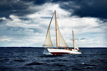 Old wooden two mast yacht sailing on waves against a shore on a windy day