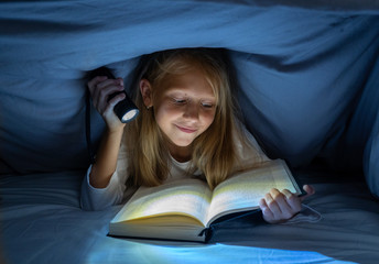 Pretty happy girl reading a book in darkness hiding under the duvet in bed with flash light