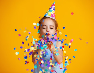 happy birthday child girl with confetti on yellow background.