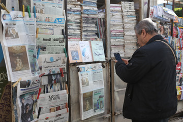 A man takes a picture of the last print of Lebanese daily newspaper Al-Mustaqbal with his mobile phone in front of a kiosk in Beirut