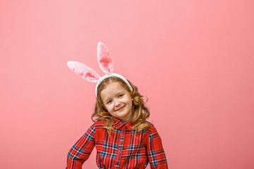 Cute little child girl with bunny ears on a colored background. Happy easter
