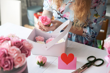Flower shop: florist girl collects a bouquet of red roses in a blue paper basket.