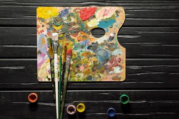 The tools of the artist, brushes, paints and palette not dark wooden background.