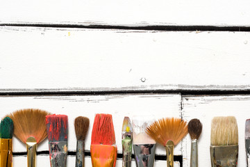 Artist's tools, dirty brushes in paint lie in a row on a white wooden background. Abstract conceptual background with place for text.