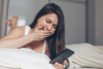 Laughing young woman with smartphone in bed at home