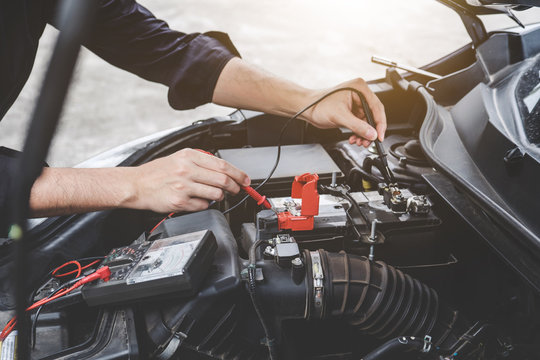 Services car engine machine concept, Automobile mechanic repairman hands checking a car engine automotive workshop with digital multimeter testing battery, car service and maintenance