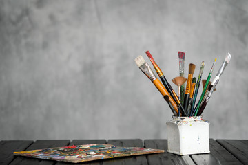 Artist's tools, brushes, paints and a palette lie on a black wooden table on a gray fabric background.