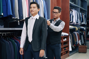 Tailor taking measurements of mature client during model fitting