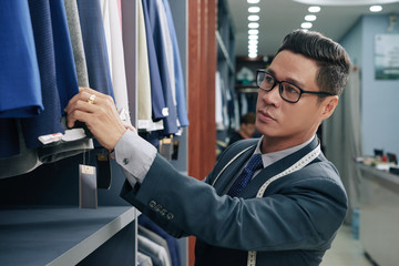 Shop assistant checking suits and jackets on rail in store