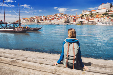 Young woman traveler looking at the Porto city, Portugal. Travel and active lifestyle concept