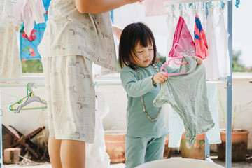 Asian little girl helps her mother to hang up clothes.
