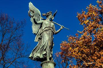 Engelstatue auf hohem Podest in den Schlossgärten Charlottenbrug Berlin mit Herbstlaub Bäumen rechts und links