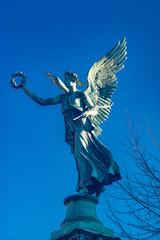 Engelstatue auf hohem Podest in den Schlossgärten Charlottenburg in Berlin