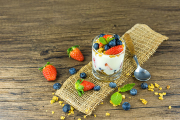 Bowl of homemade granola with Greek yogurt and fresh berries mix on wooden background from top view. Healthy blueberry and Strawberry parfait in a jar.