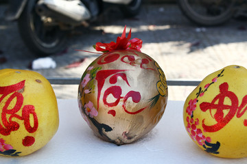 Three grapefruits decorated for celebration of Vietnamese New Year on a market in Hoi An, Vietnam. The inscription is translated - Fortune.