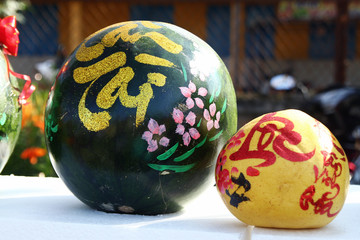 Watermelon and grapefruit decorated for celebration of Vietnamese New Year on a market in Hoi An, Vietnam. The inscription is translated  - Prosperity to you, Fortune.