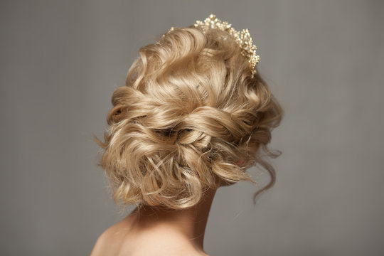 Beautiful blond girl in the image of a bride with a tiara in her hair. Picture taken in the studio on a gray background. Beauty baby face. Wedding image.