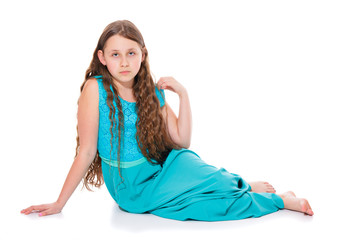 A girl of 10-11 years old in a long emerald dress with bare feet sitting on the floor. Isolation on a white background.