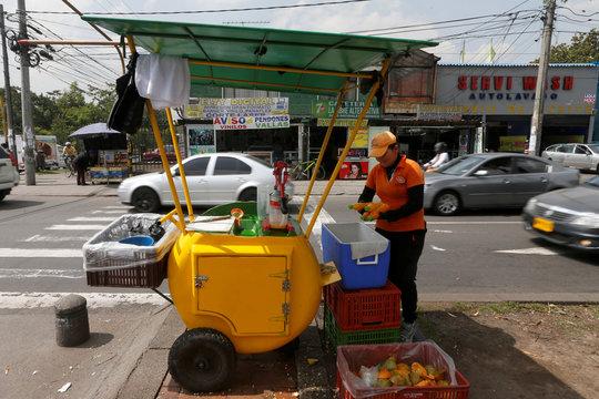 An informal worker sells orange juices at the street, in Bogota