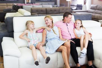 Family choosing sofa in store