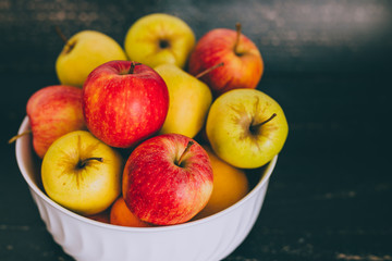 group of mixed red green and yellow apples in a white bowl on dark wood background