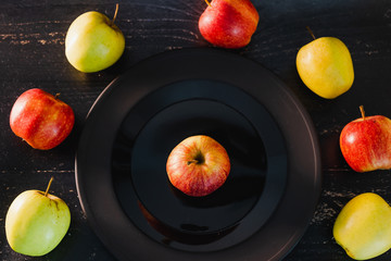 group of organic mixed colours red green and yellow apples on dark plate on black background