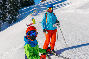 Cute skier boy with his mother in a winter ski resort.