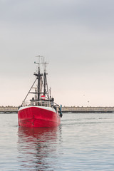 Red fishing vessel swimming in the dock and its reflection in water