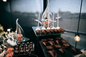 Luxury cakes on wedding dessert table in restaurant on the black background
