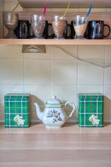 Detailfoto Kücheneinrichtung mit Teekanne und verschiedenen schottisch karierten Dosen und Gläsern für Vorräte