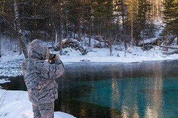 a man in camouflage winter clothes, taking pictures on a smartphone lake with a colorful turquoise bottom in the forest